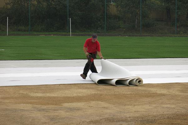 wykładanie sztucznej trawy na boisko